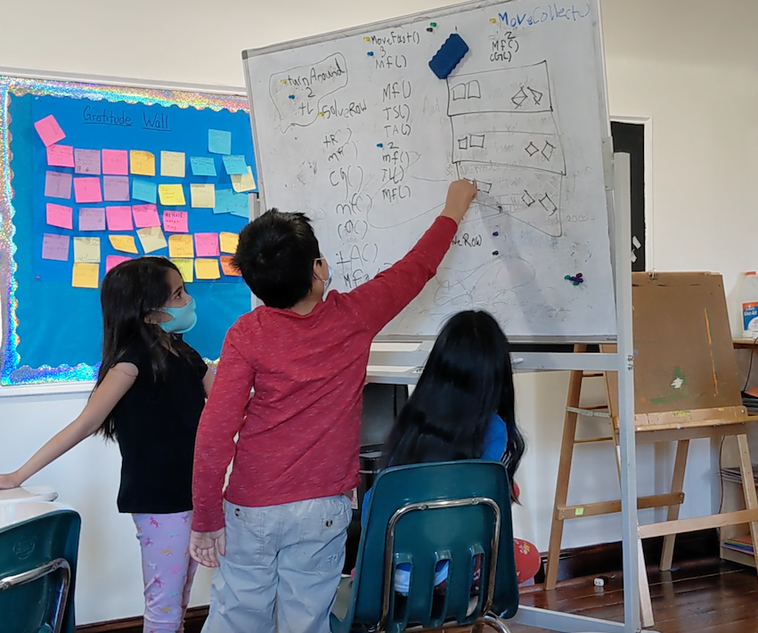Kids working on the whiteboard during the coding on an iPad class